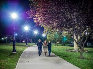 Photo of students walking on path lit by streetlamps
