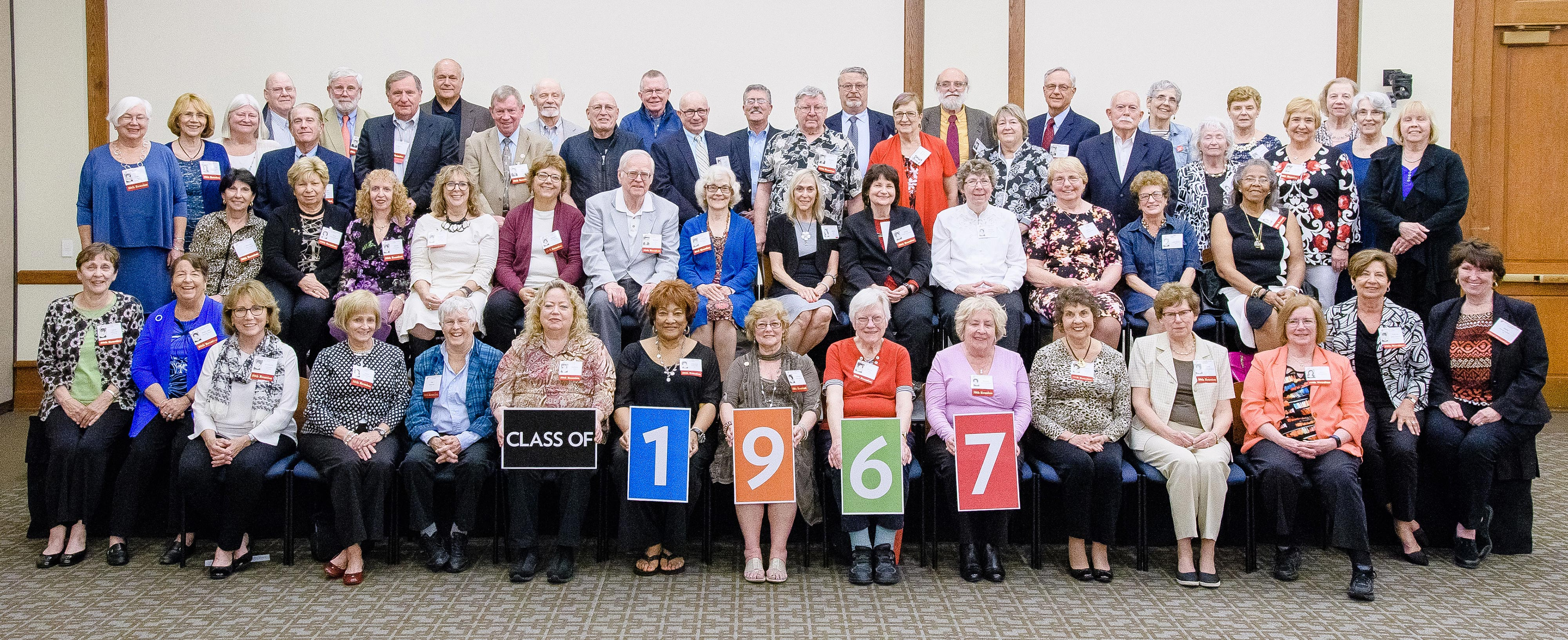 Group picture of the class of 1967 at their 50th reunion. Four members at the bottom row hold up posters that spell out 1967.