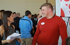 photo of student talking with company rep at job fair.