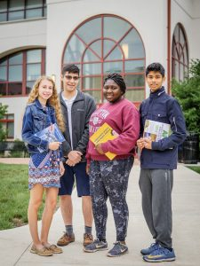 Four high school students standing outside of Schmitt Hall at Montclair State University