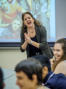 Smiling professor makes students laugh in class