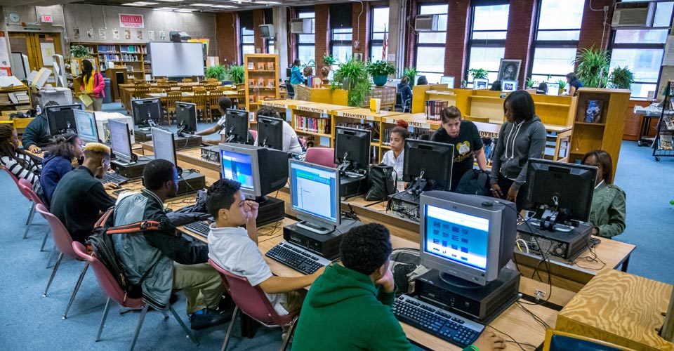 Photo of students using computer stations in the school library.