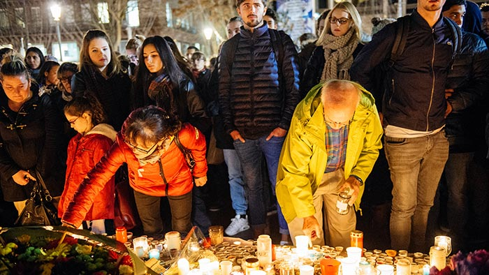 Mourners place candles at a memorial for victims of the 2015 Paris terror attacks.