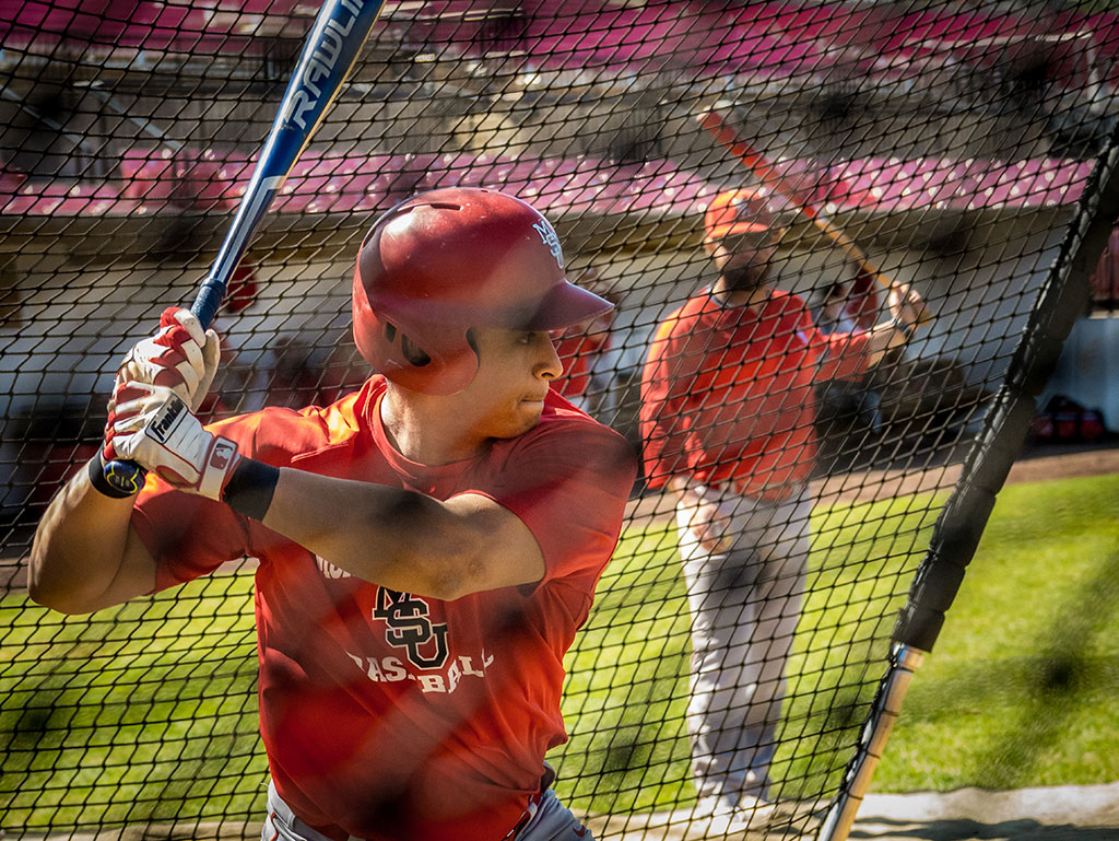 Jesse Baiza swinging baseball bat in batting cage.