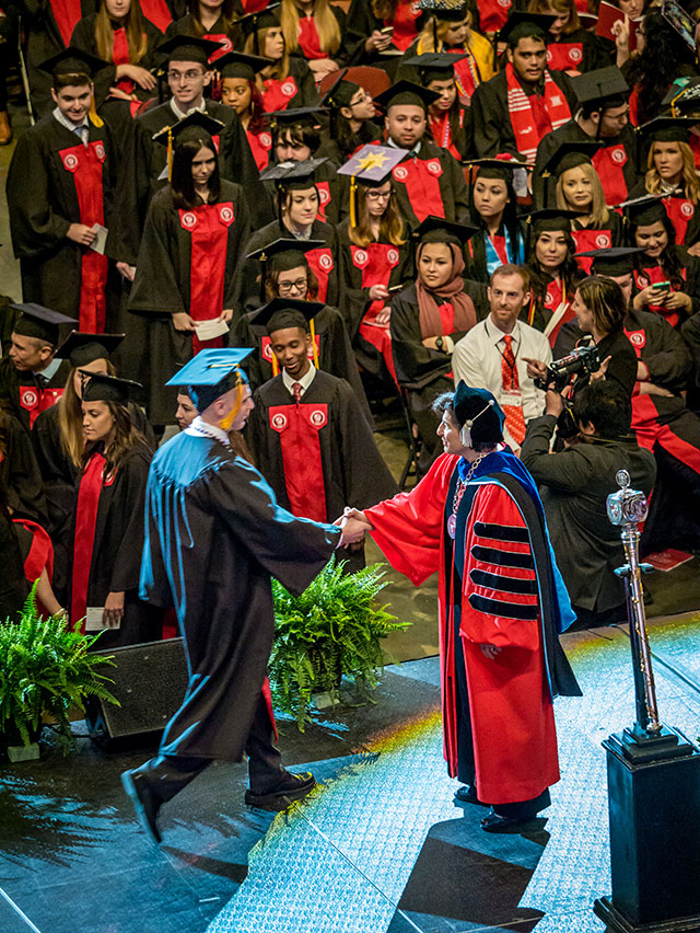 President Susan A. Cole greeting student as he crosses stage at Commencement.