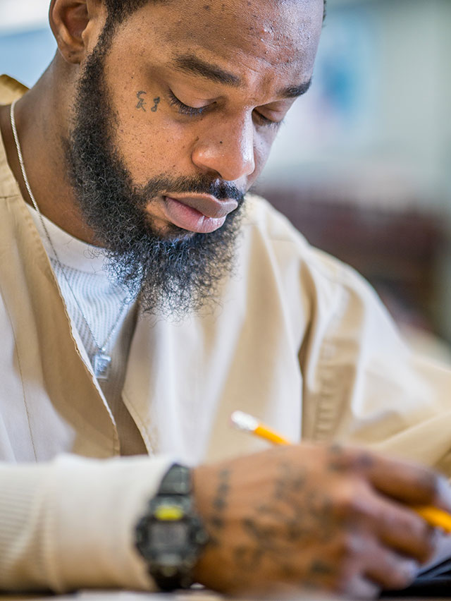 Inmate Edward Hawkins concentrates on a math problem.