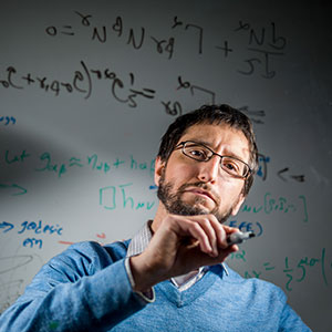 Photo of Marc Favata writing equations on glass.