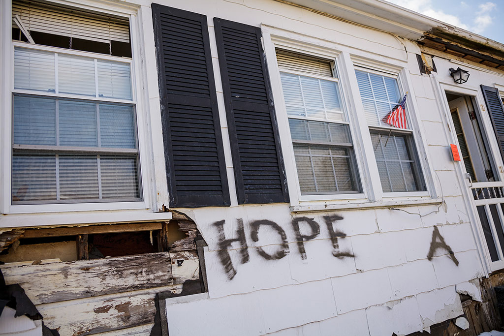 "Photo of rundown house with the word ""Hope"" written on front of it."
