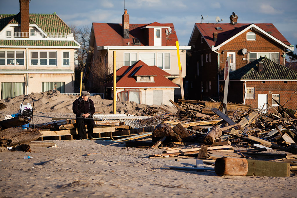 Elderly man sitting amidst ruins left by Hurricane Sandy.