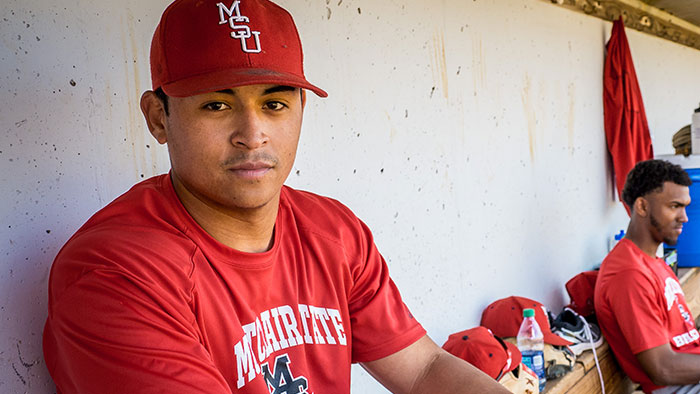 Photo of Jesse Baiza clad in baseball uniform sitting in dugout.