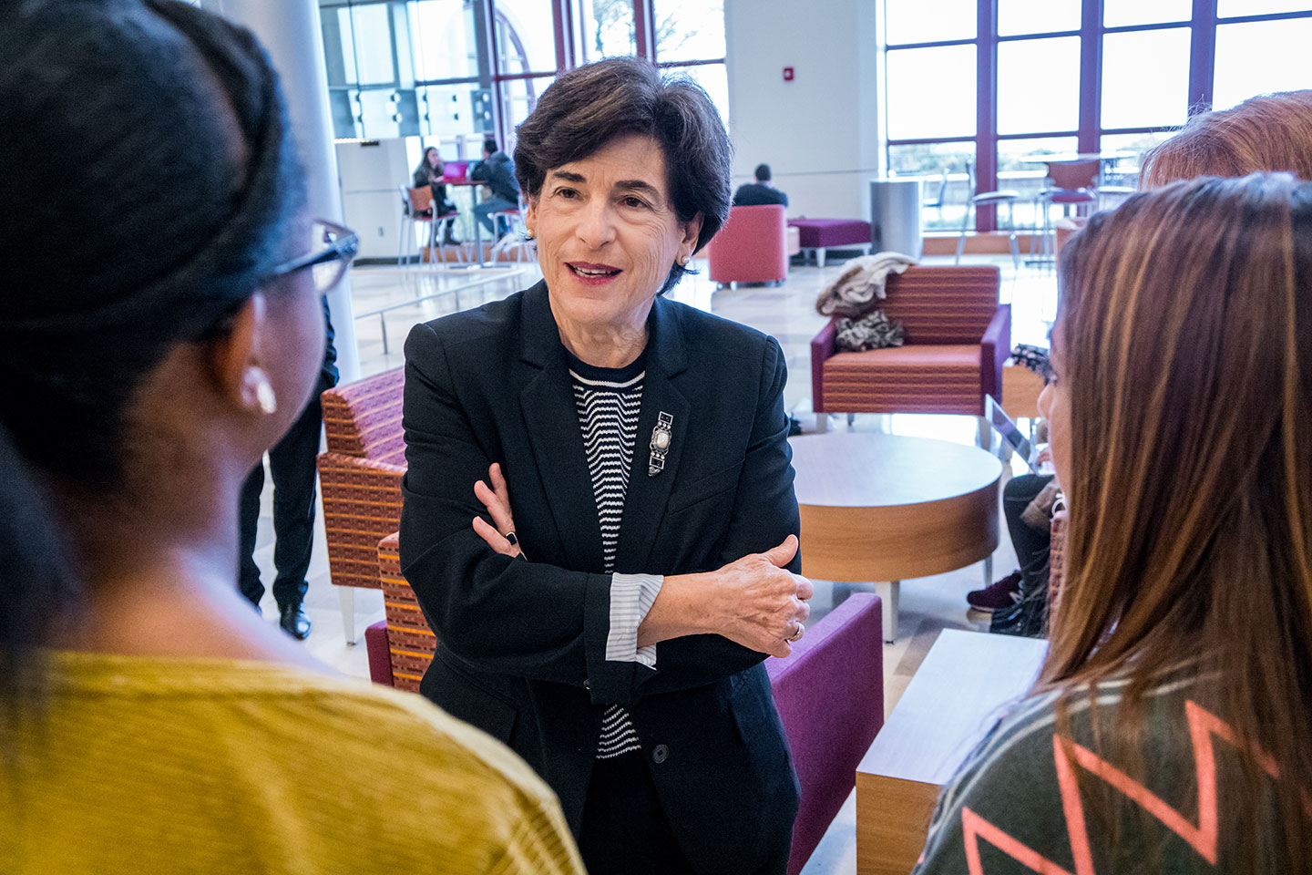 President Susan A. Cole speaking with a couple of female students.