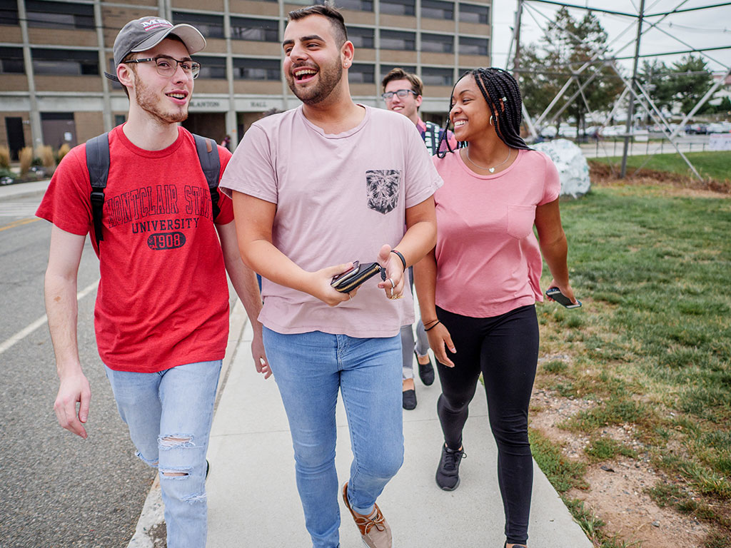 Three Montclair State University students walking and smiling.