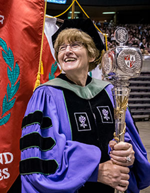Photo of Domenica Desiderioscioli, clad in Commencement gown and holding scepter.