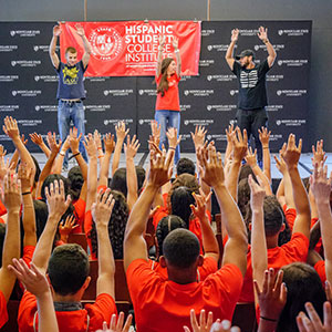 Students of Hispanic Student College Institute raising hands in air with performers on stage doing the same in front of them.
