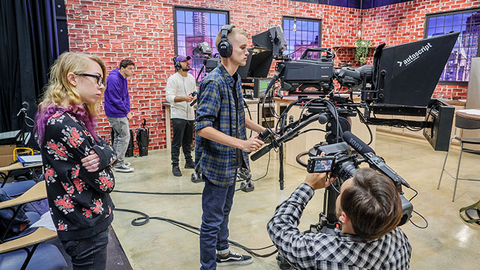 Students on set with film equipment in School of Communication and Media's new media production facility.