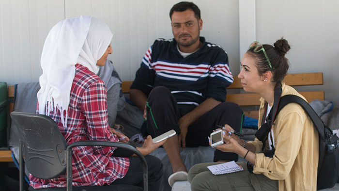 Student interviewing refugees in Greece.