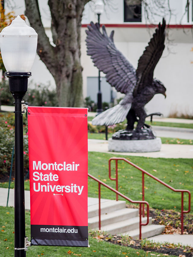 Montclair State University's banner on lightpole, with Red Hawk Statue in background.