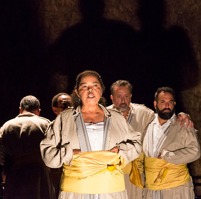 "Lynda Gravatt (Shylock No. 3) delivers Shylock's famous speech ""Hath not a Jew eyes?"" surrounded by, from left, Shylock No. 5 (Steven Skybell), Shylock No. 4 (Michael Rogers), Shylock No. 2 (Frank Rodriguez), and Shylock No. 1 (Sorab Wadia)."