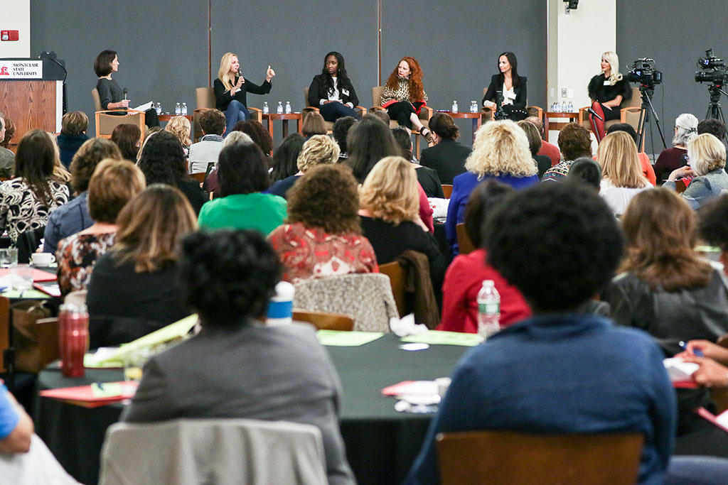 A panel of female entrepreneurs speaking in front of crowd.