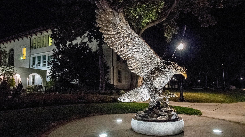 Red Hawk statue at night