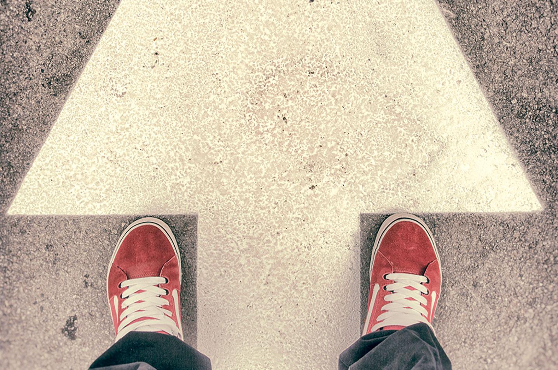 Feet standing on arrow on street