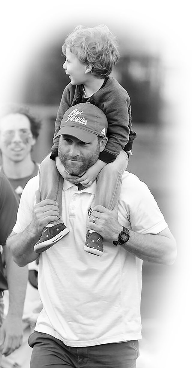 Coach Schambach with son on his shoulders.