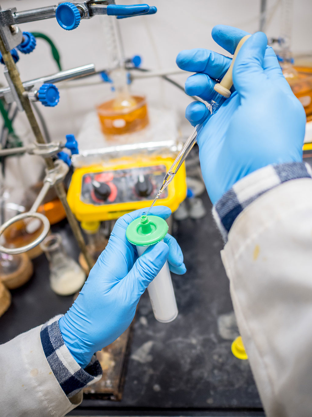 Gloved lab technicians hands injecting something into bottle