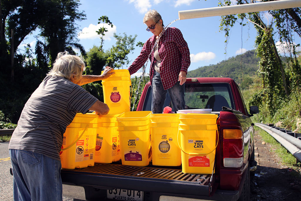 Two women collect water in cat litter buckets from a pipe bringing untreated water from the mountainside outside Utuado, Puerto Rico, three months after Hurricane Maria.