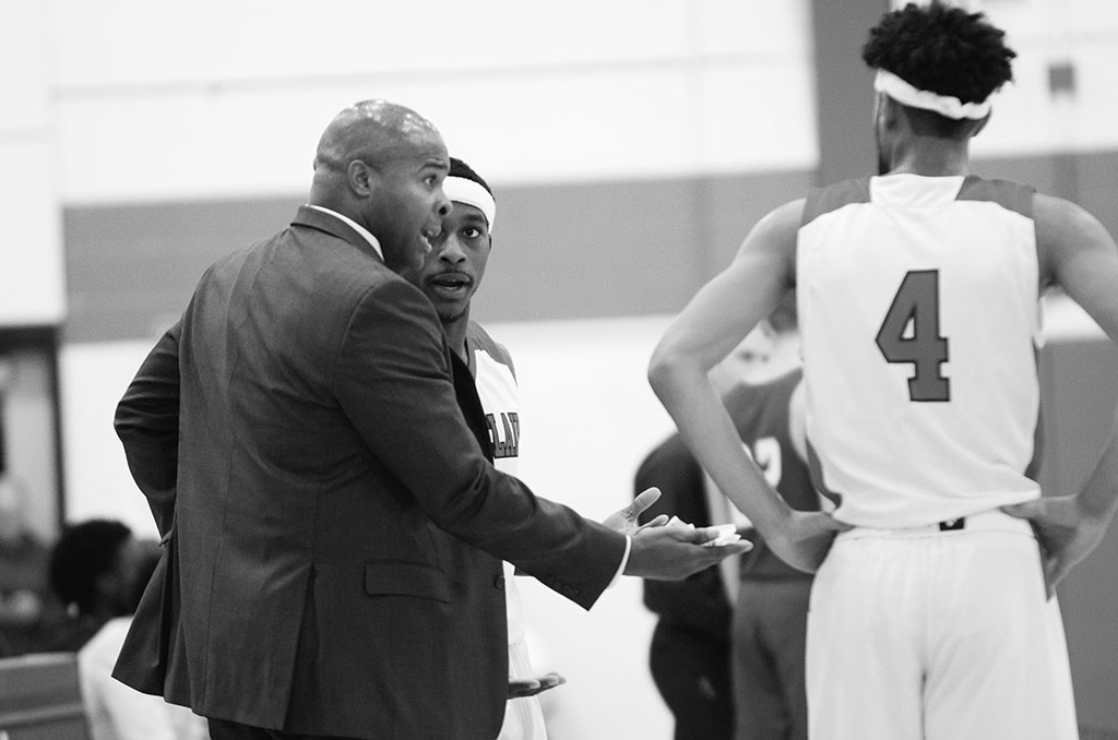 Coach Marlon Sears encourages players during a close game, prior to victory.