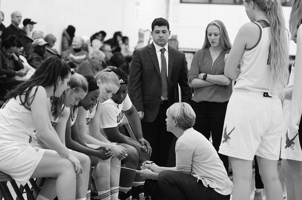 Coach Karin Harvey discusses strategy with the team during the last game of a building season.