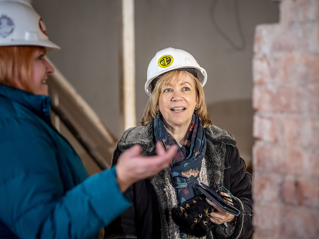 Lorraine Arnold '11, a buildings archaeologist/genealogist, returned to her alma mater to see firsthand the College Hall renovations and to assist in the search for descendants of the bricklayers. She is shown with Sharon Mahoney, the University's director of construction management.