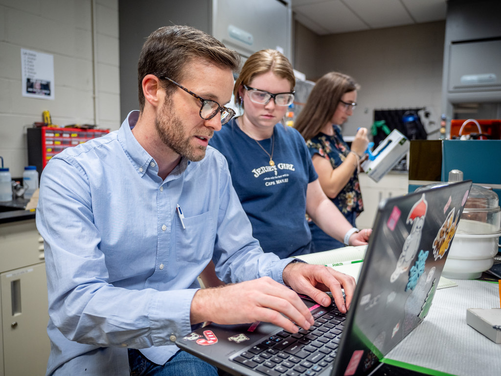 O'Neil works on chemistry experiments with senior Kelly Obrzut (center) and junior Katherine Schaffer (right) in his lab. Schaffer is part of the team working to create tools to measure neurotransmitter pathways.