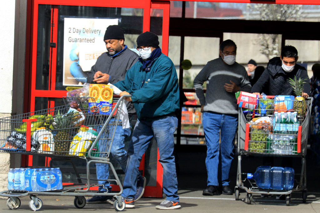 "Shoppers stocked up on food supplies in Paramus. Many wore masks and gloves and practiced social distancing. Bottom: Hundreds of cars lined up at the Bergen Community College testing site predawn, before authorities closed down the entrances less than an hour before it reached ""maximum capacity."""