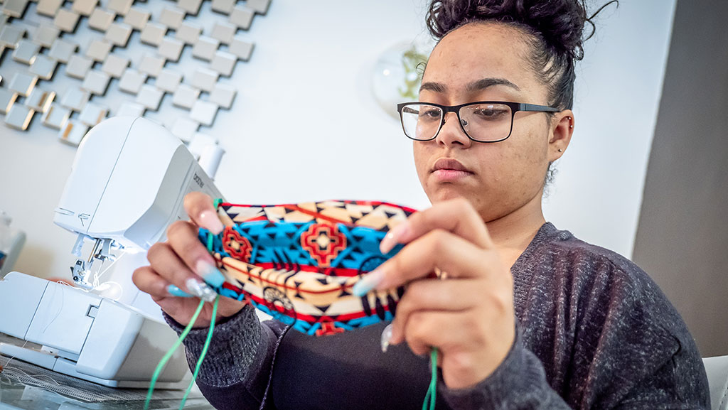 Awilda Quezada Puntiel puts the finishing touches on a handmade mask.