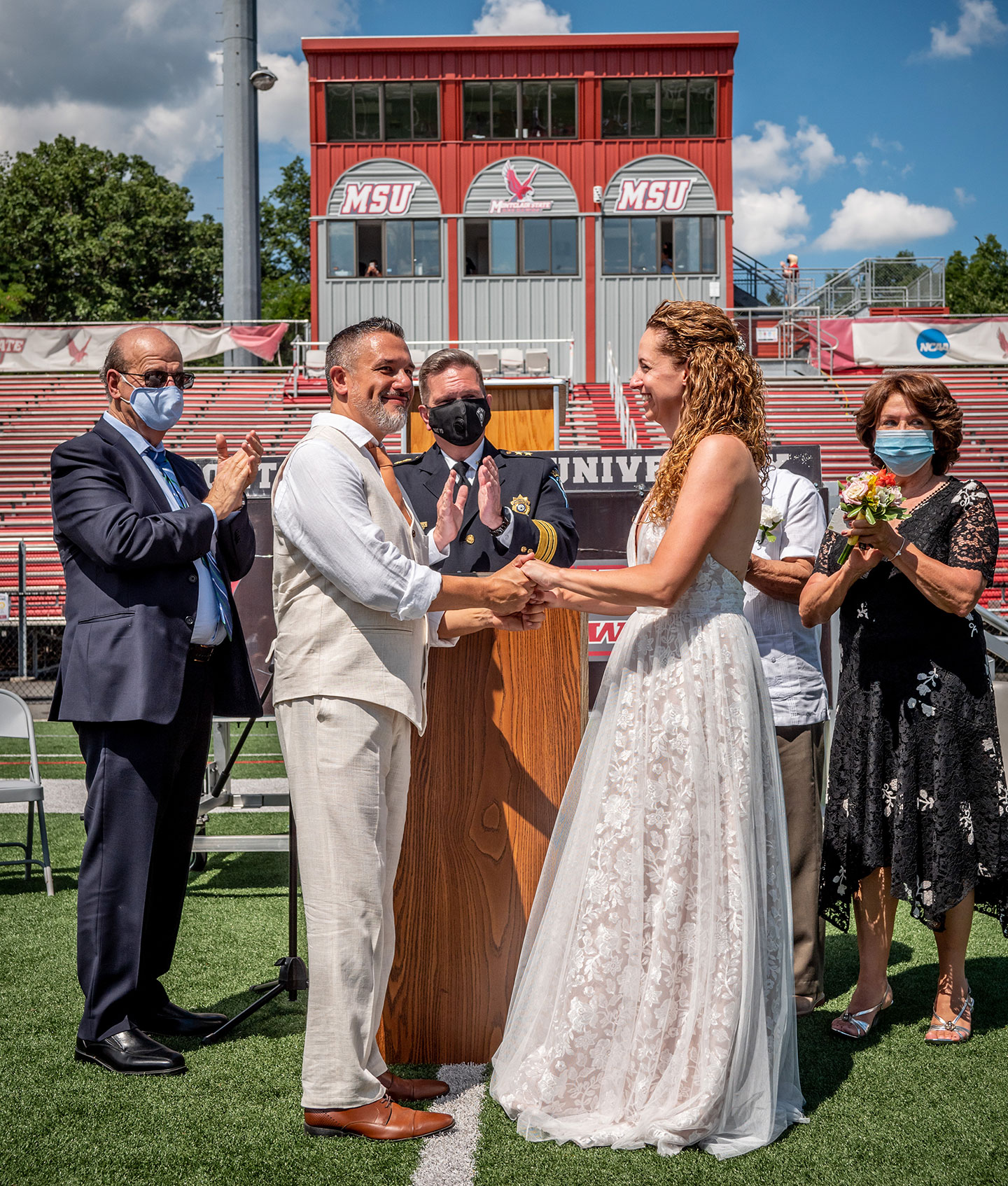 Chief of University Police Paul Cell officiates the wedding of Janet Fenner and Gregory Dabice on the Montclair State 50-yard line.