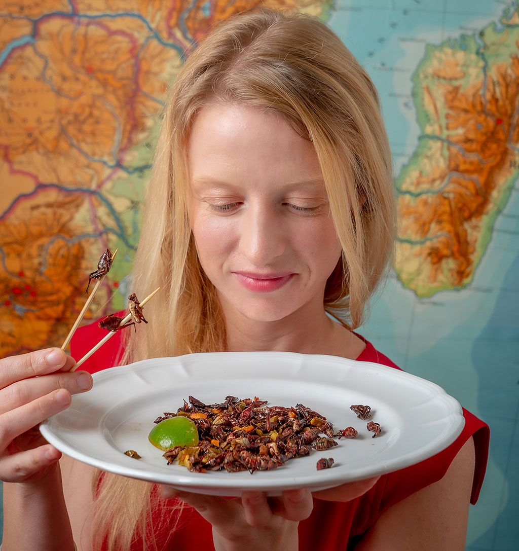 """Cortni Borgerson, seen here with a plate of grasshoppers, leads a program to farm the so-called """"bacon bugs"""" in Madagascar to improve food security."""