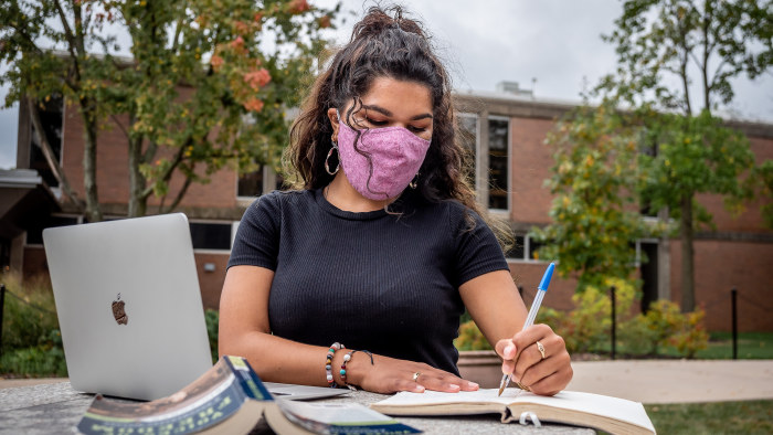 Student wearing mask writing in notebook outside in front of laptop
