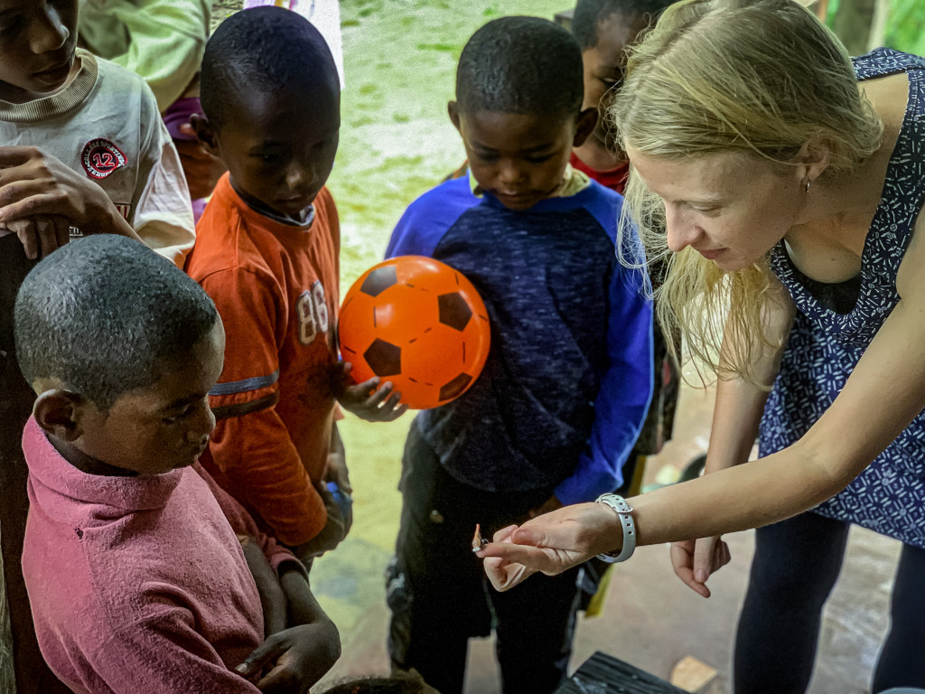 8. Borgerson shows some Malagasy children a sakondry insect.
