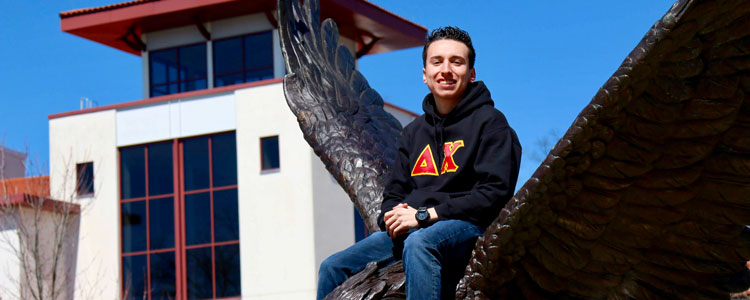 Picture of Brian Cadavid sitting on the campus Hawk statue.