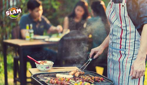 Picture of a person in an apron cooking on an outdoor grill.