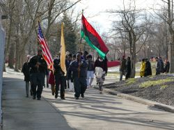 Photo of people marching on campus and holding flags