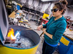 Photo of student using blowtorch to melt copper for sculpture.