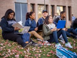 Group of students sitting outside and smiling