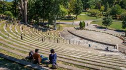Photo of students sitting in outdoor amphitheater.
