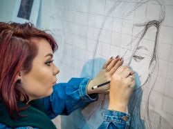 Student drawing a portrait with pencil on large graph paper on wall at the College of the Arts.