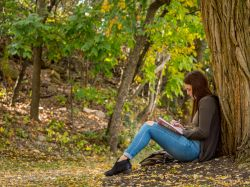 Photo of a student leaning against a tree and writing in a notebook
