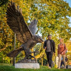 Montclair State Students walk past the Red Hawk statue