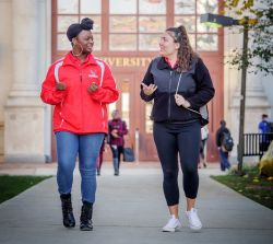 photo of Red Hawk for a Day Host and student outside University Hall