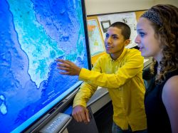 Photo of two students using interactive map screens in the ADP Center.