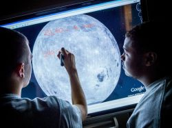 student annotating back-lit photo of the moon